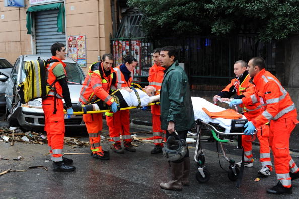 Rescuers carry a person injured on a str