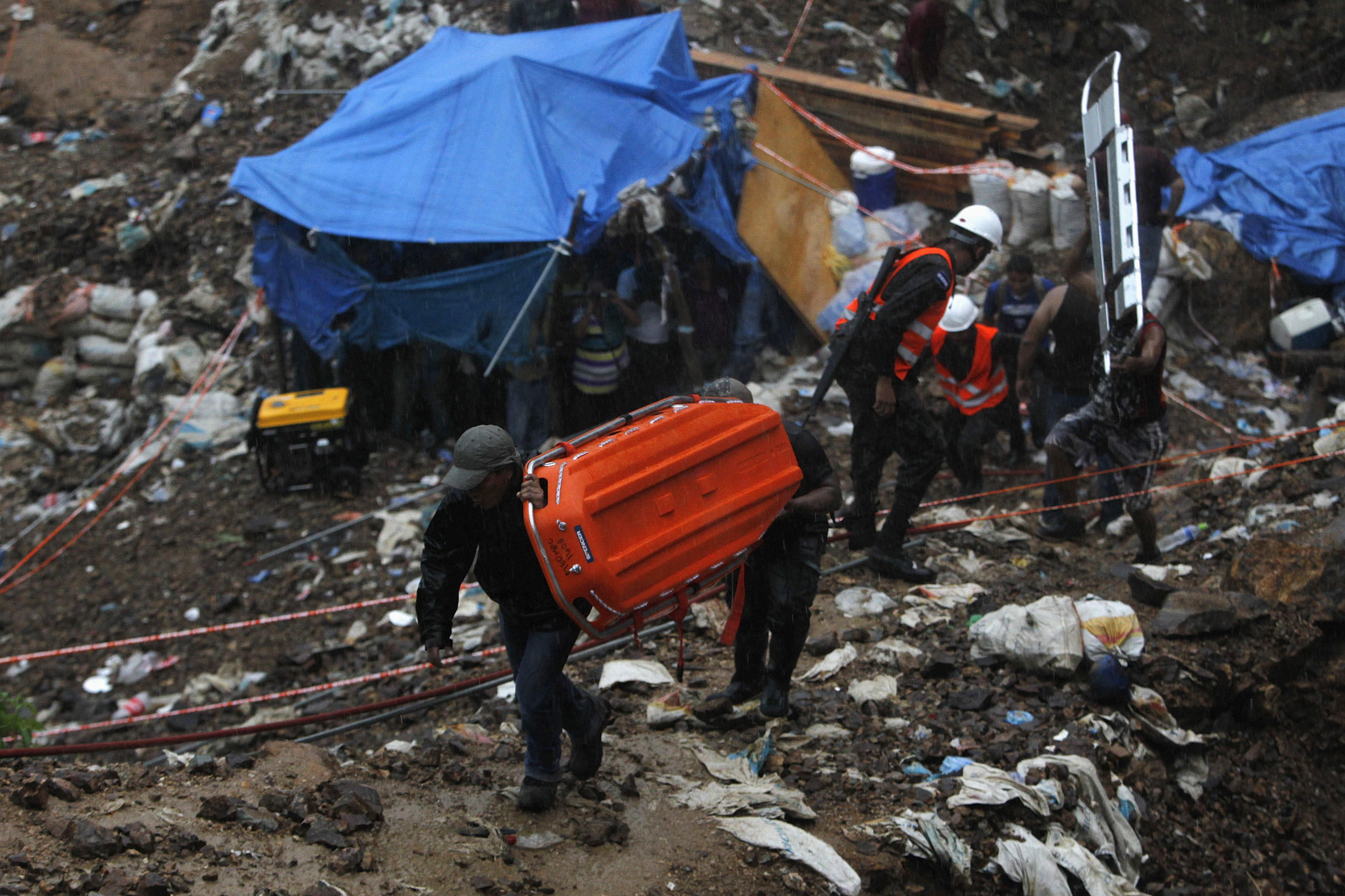 Miners carry stretchers as other take cover from rain in a makeshift tent at the site of a landslide at a gold mine in San Juan Arriba