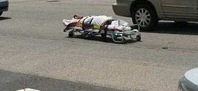 A stretcher with a dead body fell out of a coroner's vehicle
