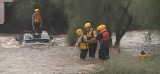 Firefighters rescue a driver trapped in a flooded wash
