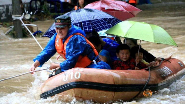 floods-china-2016-a-rescuer-grabs-a-rope-to