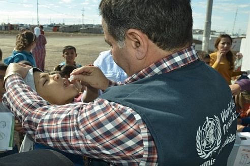 6 A young student receives his first oral cholera vaccination dose from WHO's Dr Salahuddin Hussein, a medical officer working in Dohuk Governate, Iraq.