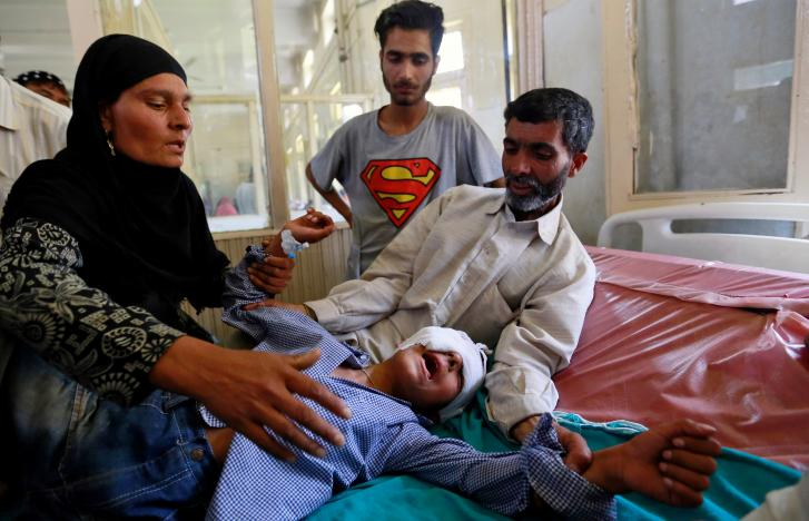Parents comfort their son whom they say was injured by pellets shot by security forces in Srinagar following weeks of violence in Kashmir